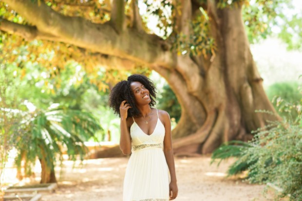 smiling-dreamy-black-woman-walking-park_1262-6254